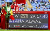 2016 Rio Olympics - Athletics - Final - Women's 10,000m Final - Olympic Stadium - Rio de Janeiro, Brazil - 12/08/2016. Almaz Ayana (ETH) of Ethiopia poses next to a display with her timing after setting a new world record.    REUTERS/Lucy Nicholson